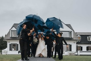 wedding-ceremony-in-the-rain-bride-and-father-walking-to-tent-with-staff-holding-umbrellas