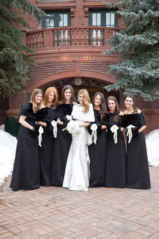 bridesmaids-in-black-long-dresses-with-fur-hand-warmer-muffs-and-fur-wrap-shawls
