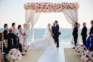 bride-in-galia-lahav-wedding-dress-with-groom-in-colored-suit-under-pink-white-chuppah-beach-wedding
