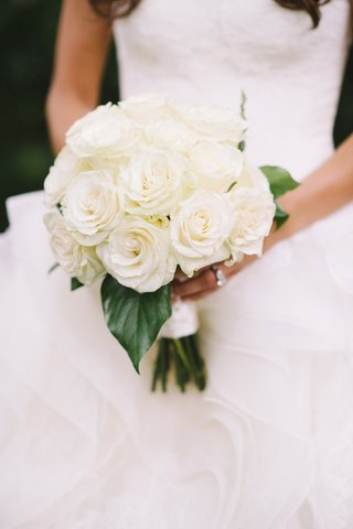 bride-holding-white-roses-and-large-leaves