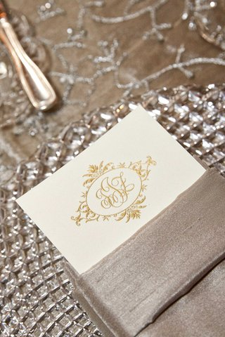 menu-card-on-ivory-stationery-with-gold-script-monogram-inside-napkin-on-crystal-charger
