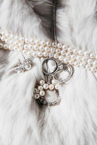 pearl-three-strand-bracelet-pearl-earrings-and-diamond-rings-on-fur-shawl