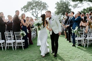 outdoor-destination-wedding-ceremony-hawaii-kiss-white-crepe-dress-and-tuxedo-jacket-grass-lawn-kiss