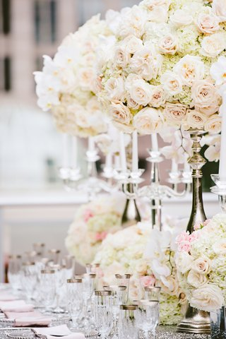 wedding-reception-table-with-tall-silver-stands-low-vases-with-white-hydrangeas-orchids-pink-roses