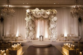 wedding-furniture-gold-on-both-sides-of-chuppah-with-white-flower-accents-candlelight-lit-up-boxes