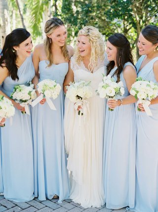 bride-in-lace-wedding-dress-with-bridesmaids-in-long-light-pastel-blue-bridesmaid-dresses