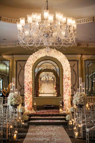 flower-arch-and-petal-aisle-under-crystal-chandelier