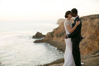 bride-groom-kiss-cliffside-southern-california-wedding-chic-dress-ocean-rocks-venue