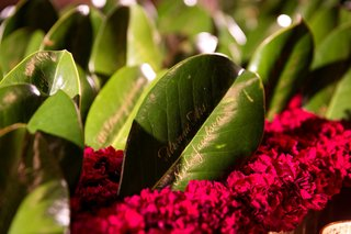wedding-details-ideas-real-greenery-leaf-with-gold-calligraphy-on-bed-of-red-flowers
