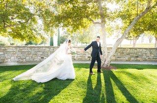 groom-leads-bride-outside-park-setting-catholic-wedding-california-garden-black-suit-long-veil