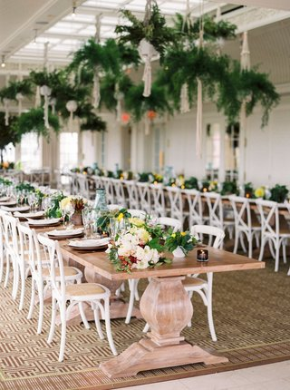 wedding-reception-wood-pedestal-table-white-chairs-with-long-flower-low-centerpiece-and-bottles-fern