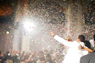 bride-and-groom-with-guests-dancing-and-singing-confetti-cannon-explosion-in-air-red-white-blue