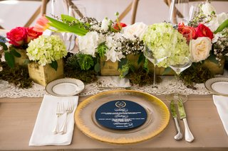 blue-round-menu-card-on-gold-charger-plate-on-wood-table-with-pink-red-and-white-flowers