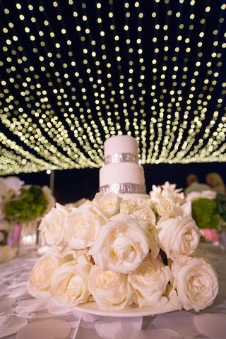 mini-wedding-cake-with-silver-details-on-bed-of-ivory-roses