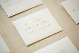 white-stationery-seating-cards-with-handwritten-gold-names
