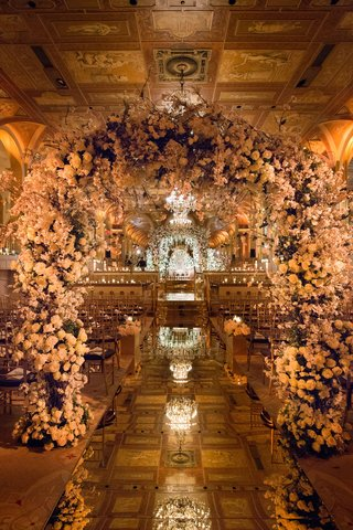 mirror-aisle-runner-with-flower-arches-and-tiled-ceiling-at-the-plaza-hotel-with-chandeliers-flowers