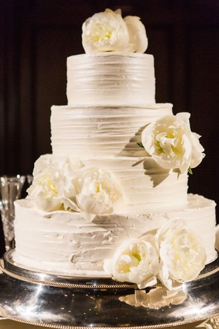 four-layer-buttercream-frosting-wedding-cake-with-fresh-flowers-peony-blooms-on-top-and-tier-lemon