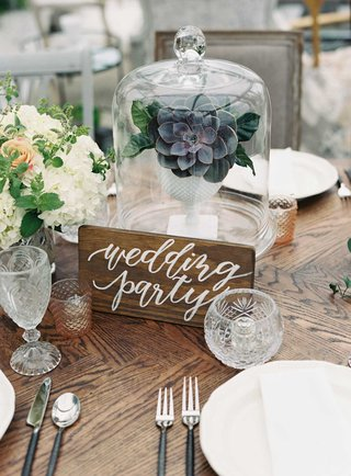 calligraphy-wood-sign-on-wood-reception-table-succulent-in-glass-dome-white-hydrangea-orange-rose