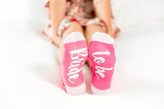 wedding-gift-ideas-pink-and-white-socks-for-bride-with-bride-to-be-on-sole-of-foot-bottom-sock