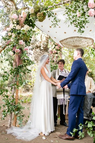 bride-in-jenny-packham-dress-and-dear-maradee-veil-holds-grooms-hands-under-outdoor-chuppah-jewish