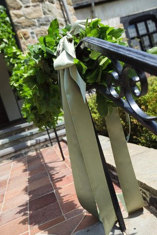 handrail-decorated-with-an-olive-green-ribbon-and-greenery-garland-at-a-wedding