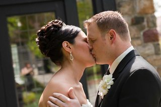 bride-with-an-updo-kisses-groom-wearing-a-black-tuxedo-and-orchid-boutonniere