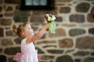 flower-girl-in-a-sleeveless-pink-dress-presents-a-bouquet-of-red-and-white-flowers