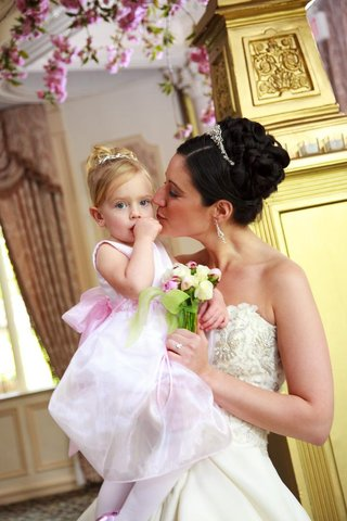 bride-in-a-monique-lhuillier-gown-carries-a-flower-girl-in-a-pink-sleeveless-dress-and-tiara
