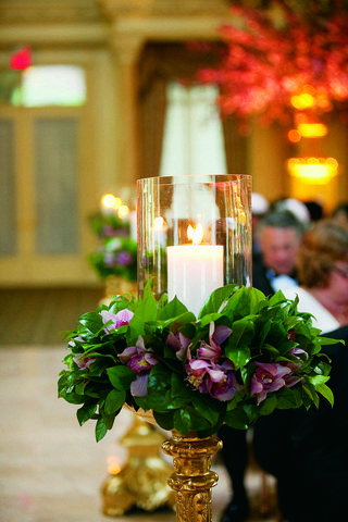 wedding-ceremony-with-candles-in-glass-hurricanes-surrounded-by-purple-orchids-and-greenery