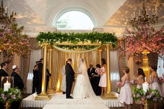 bride-in-a-monique-lhuillier-gown-and-veil-stands-with-groom-in-a-black-tuxedo-under-a-chuppah