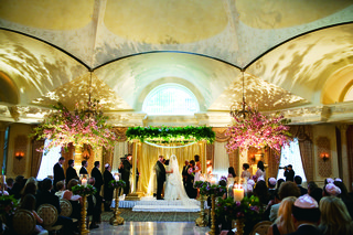 wedding-ceremony-with-a-golden-post-chuppah-and-to-urns-with-large-cherry-blossom-branches