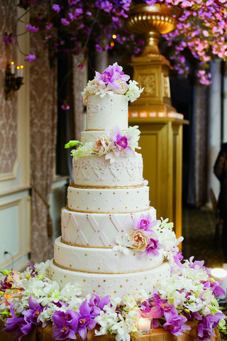 white-wedding-cake-with-understated-gold-accents-surrounded-by-white-and-purple-orchids