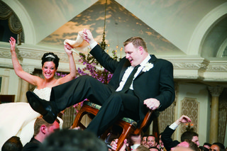 bride-in-a-monique-lhuillier-gown-and-groom-in-a-black-tuxedo-dance-the-hora