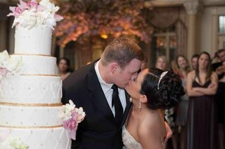 bride-and-groom-kiss-beside-a-white-and-gold-cake-with-white-and-pink-flowers