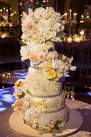 white-round-cake-with-sparkling-details-and-flowers