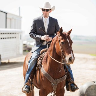 groom-in-jeans-and-suit-jacket-with-cowboy-hat-on-brown-horse