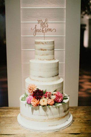 semi-naked-wedding-cake-on-wood-table-with-pink-orange-rose-dahlia-flowers-greenery-laser-cut-topper