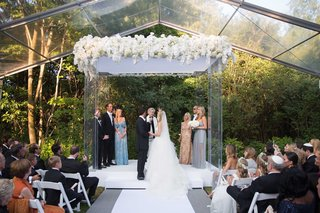 bride-and-groom-jewish-wedding-outdoor-clear-glass-tent-venue-orchid-flowers-greenery