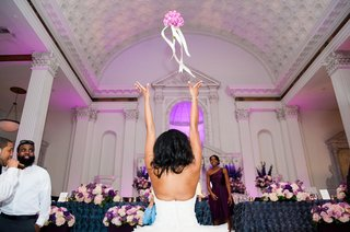 bride-tossing-pink-rose-bouquet-to-friends