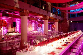 pink-lighting-and-long-white-table-with-red-floral-runner