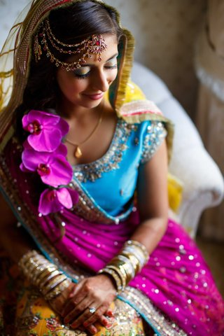 pakistani-bride-in-purple-blue-and-yellow-traditional-dress-with-headpiece-sits-and-smiles