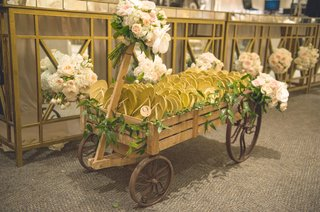 wedding-reception-with-a-wood-wagon-full-of-flip-flops-adorned-with-pink-white-roses-greenery