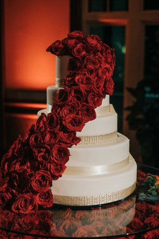 white-five-layer-wedding-cake-with-gold-banding-and-crimson-red-roses-cascading-down-layers