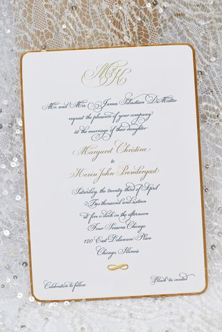 script-calligraphy-font-with-monogram-on-black-tie-wedding-invitation-on-top-of-wedding-dress