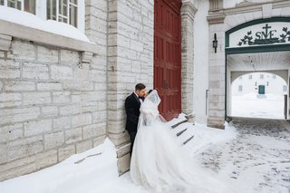 wedding-portrait-bride-and-groom-outside-winter-wedding-quebec-city-canada-stone-building-tall-doors