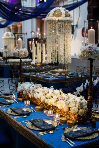 blue-and-gold-tablescape-with-low-white-floral-arrangements-and-high-hanging-centerpiece-kaleera