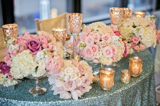 blue-sequin-tablecloth-with-gold-candle-votives-and-pink-flowers