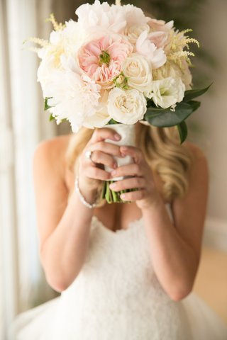 bride-hiding-her-face-with-rose-blooms-and-peonies
