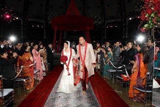 indian-newlyweds-walking-up-damask-aisle