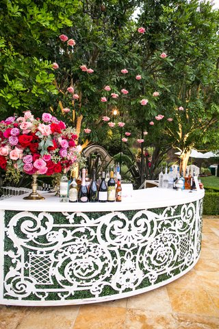 wedding-reception-backyard-wedding-curved-white-bar-with-greenery-pink-flowers-cocktail-hour